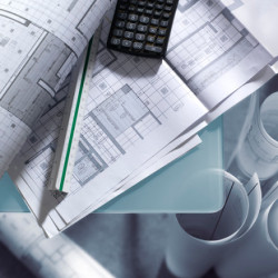 Produktfoto av ritningar, linjal och miniräknare.